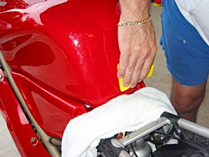 Using a sqeegee to install paint protection film on a Ducati 916