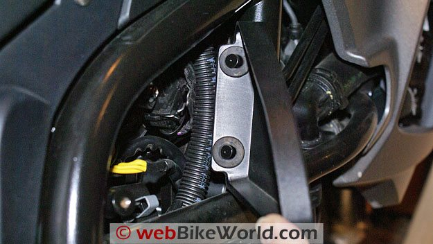 After the Torx bolt is removed on the BMW F800GS, the side cover must be pulled from these metal tangs.