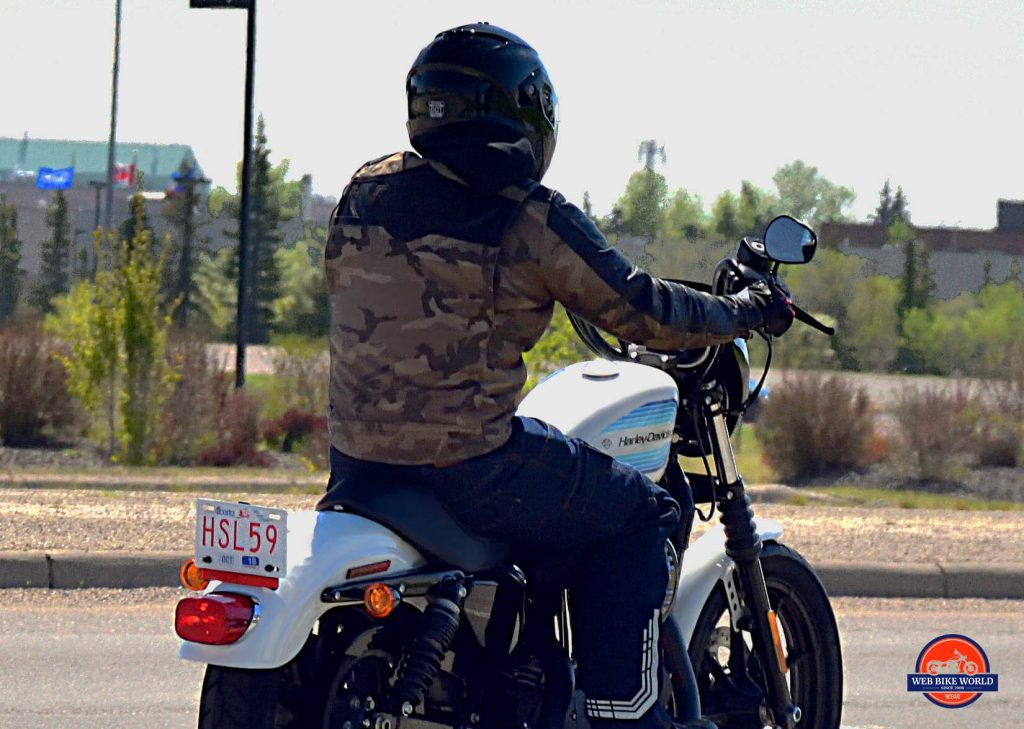Rider in Camo on top Harley Davidson Motorcycle