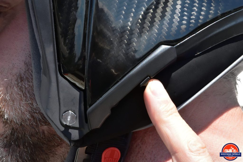 The sliding switch on the helmet for extending or retracting the sun lens.