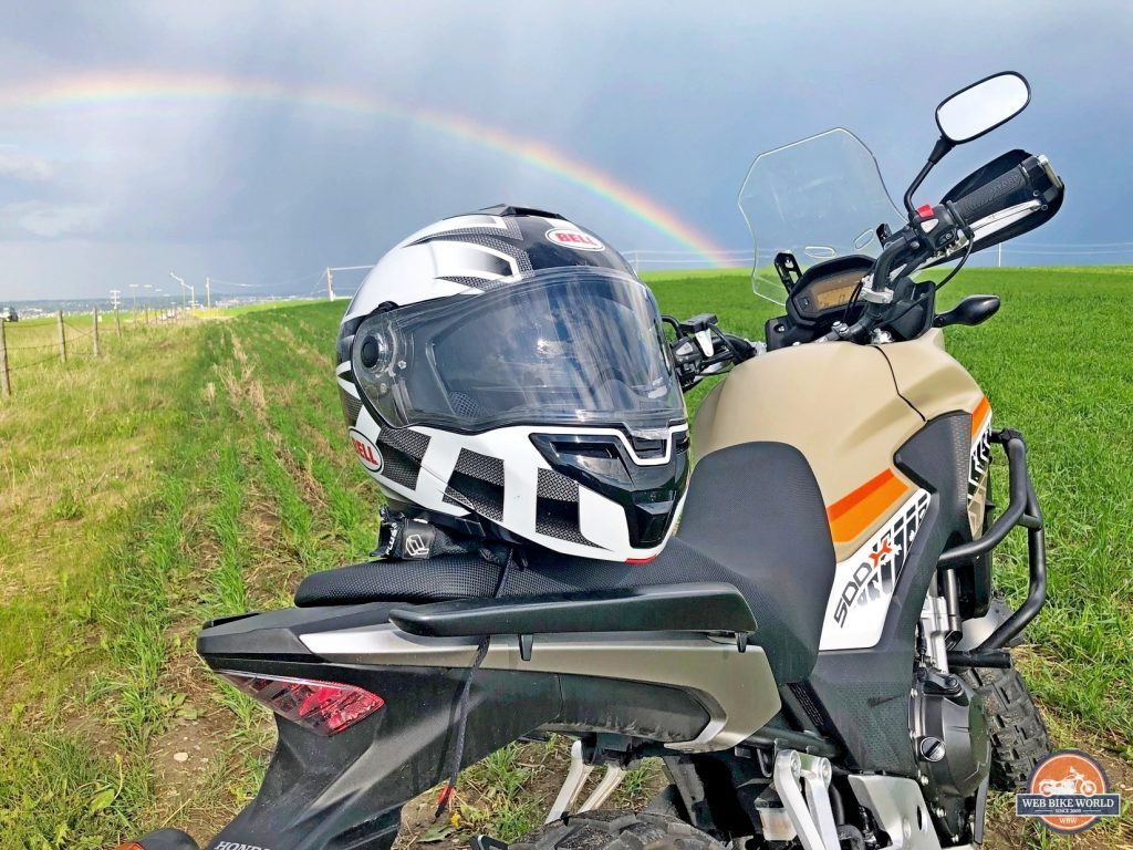 The Bell SRT Modular on a CB500X with a rainbow in the background.