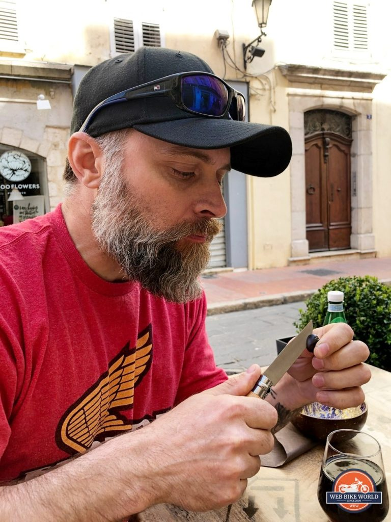 Eating an olive using an Opinel knife in Grasse, France.