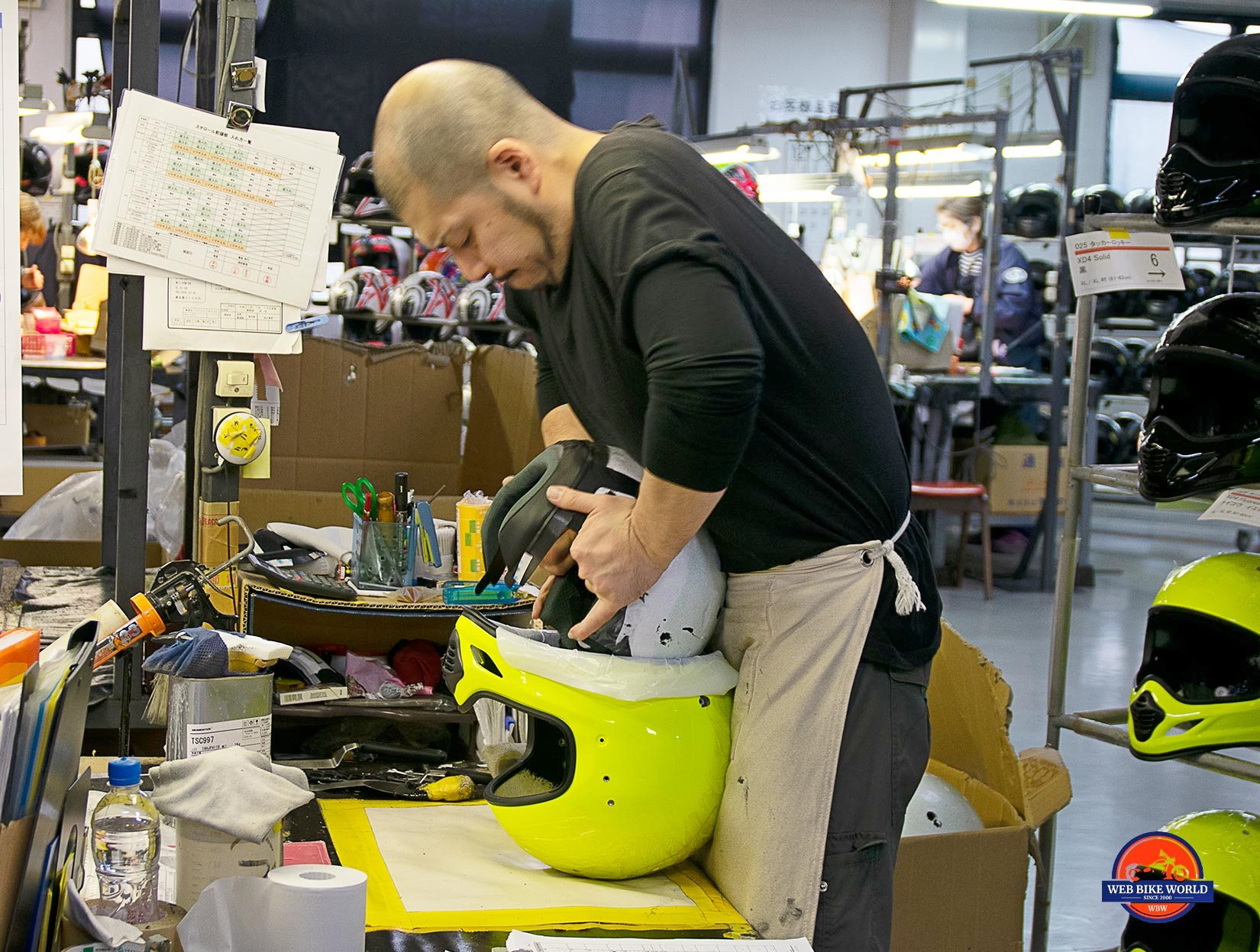 An Arai employee installs EPS foam liner in a helmet shell.
