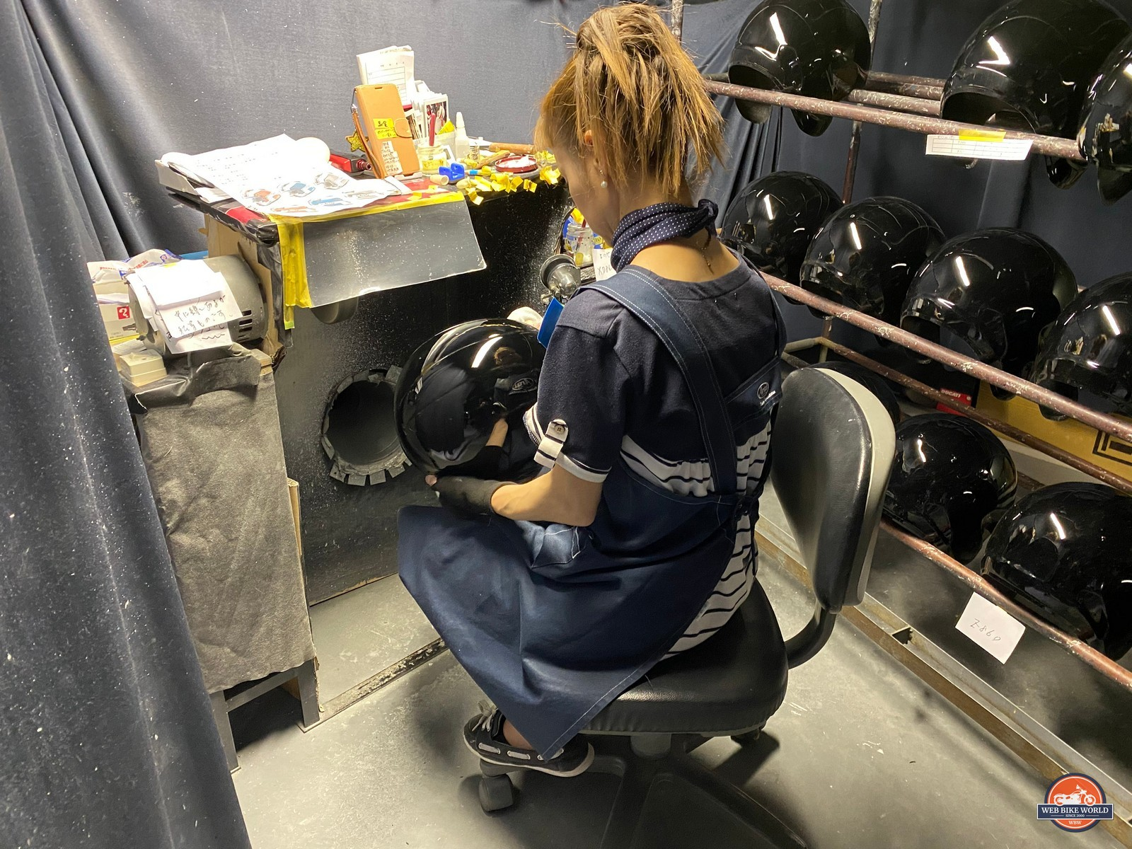 A woman polishes helmet shells at the Arai factory in Japan.