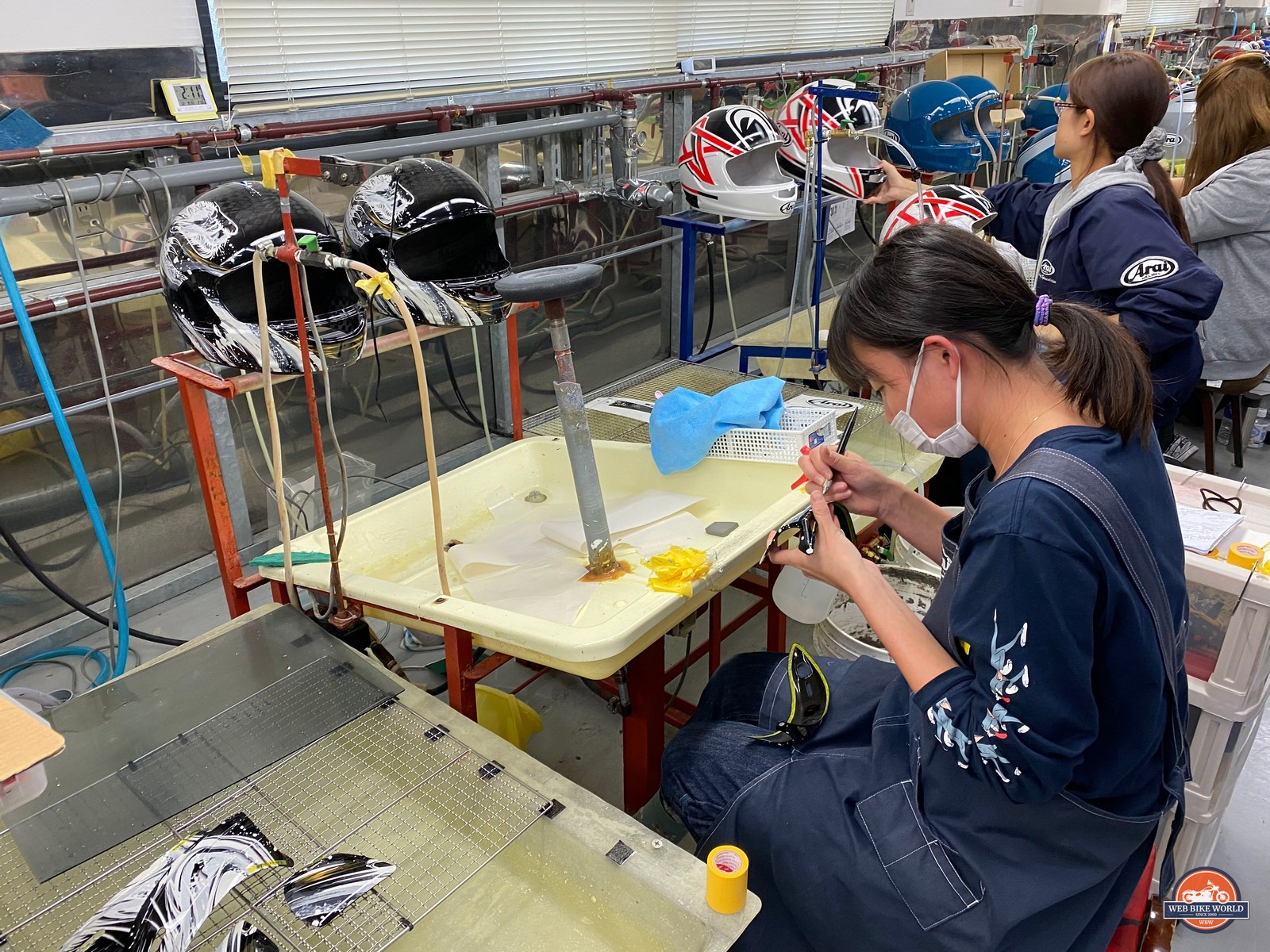 Workers carefully apply decals to helmets at the Arai factory.