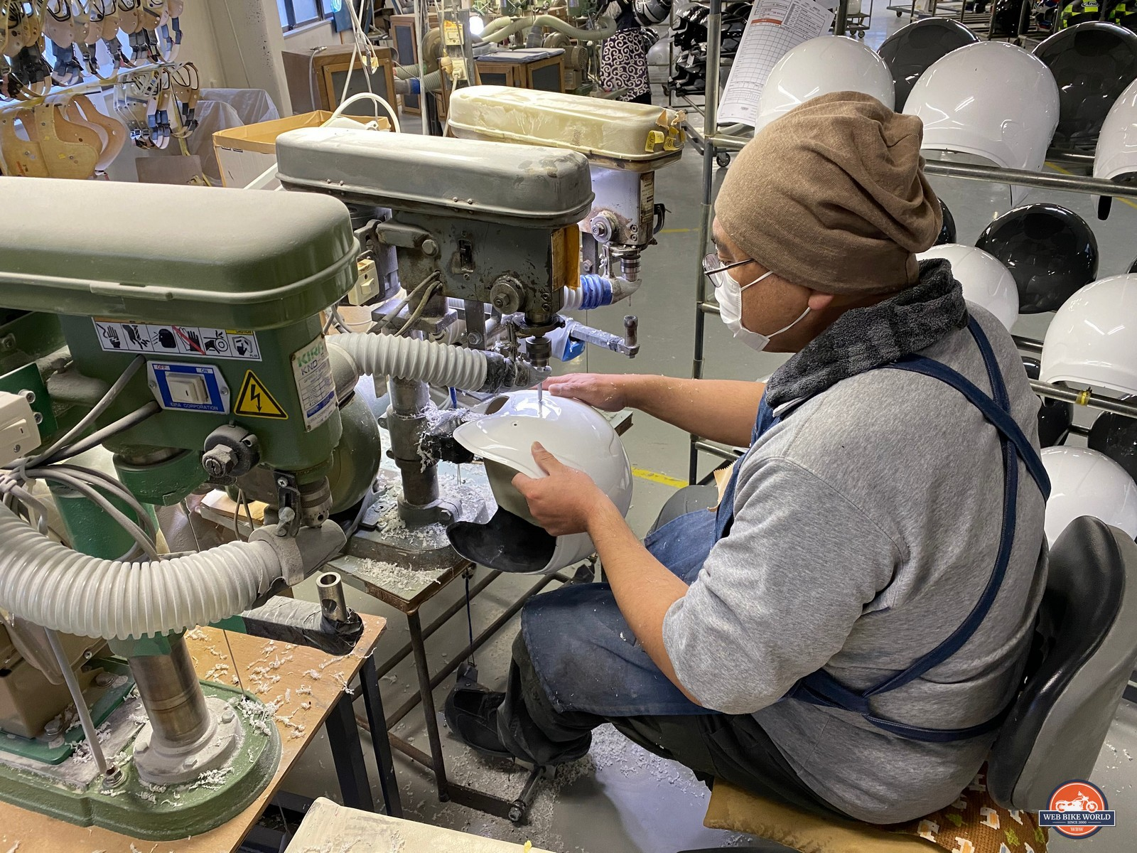 An Arai employee drills holes in a helmet shell.
