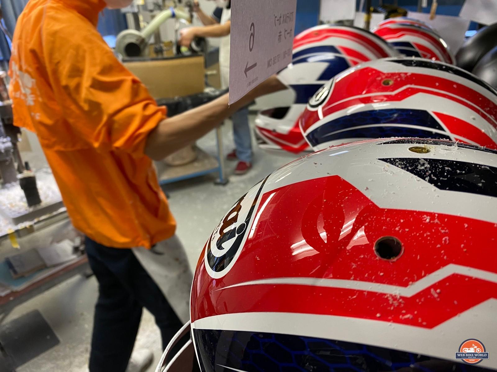 Freshly drilled ventilation holes in Arai helmet shells.