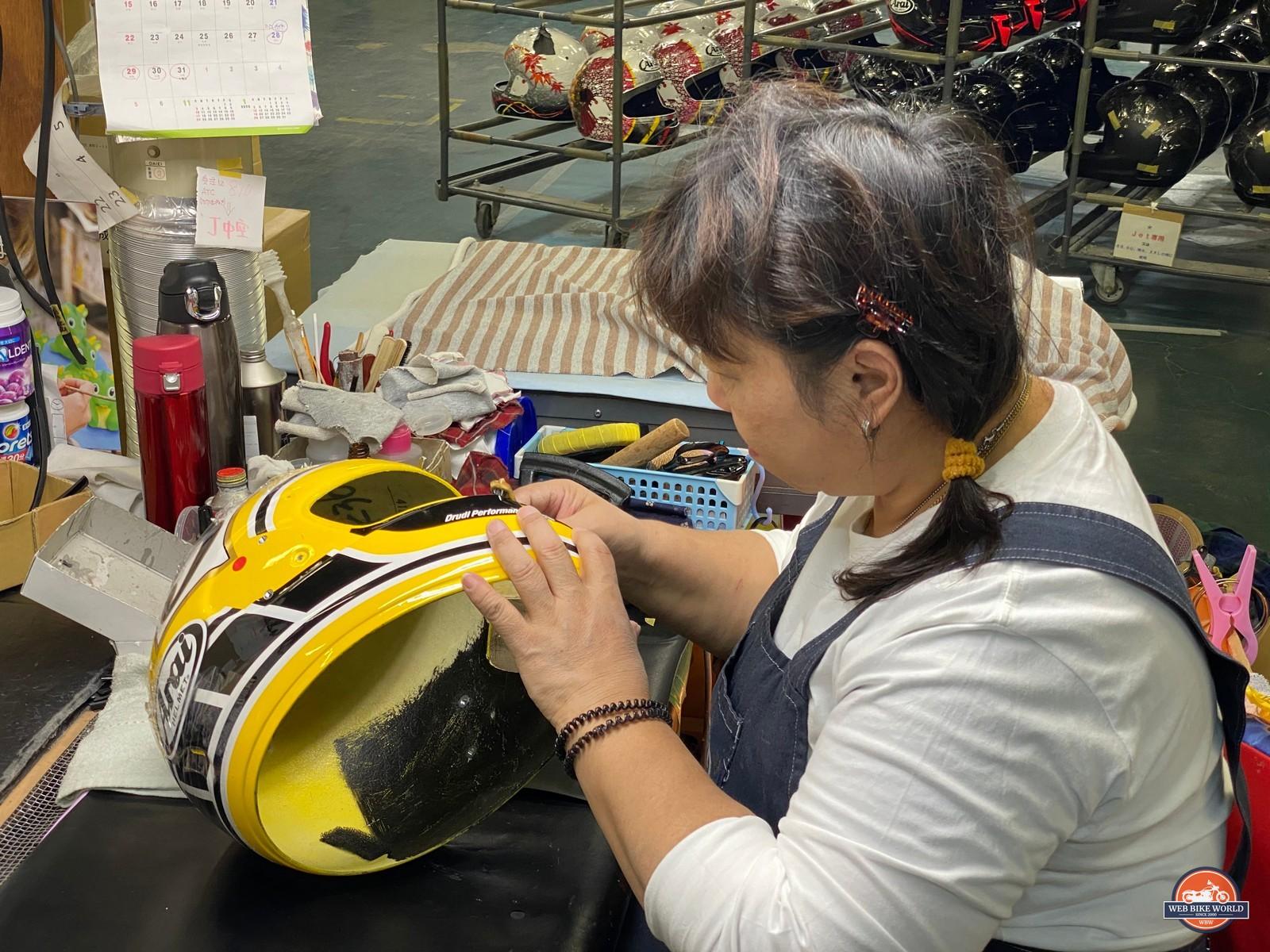An Arai helmet artisan working on a helmet.