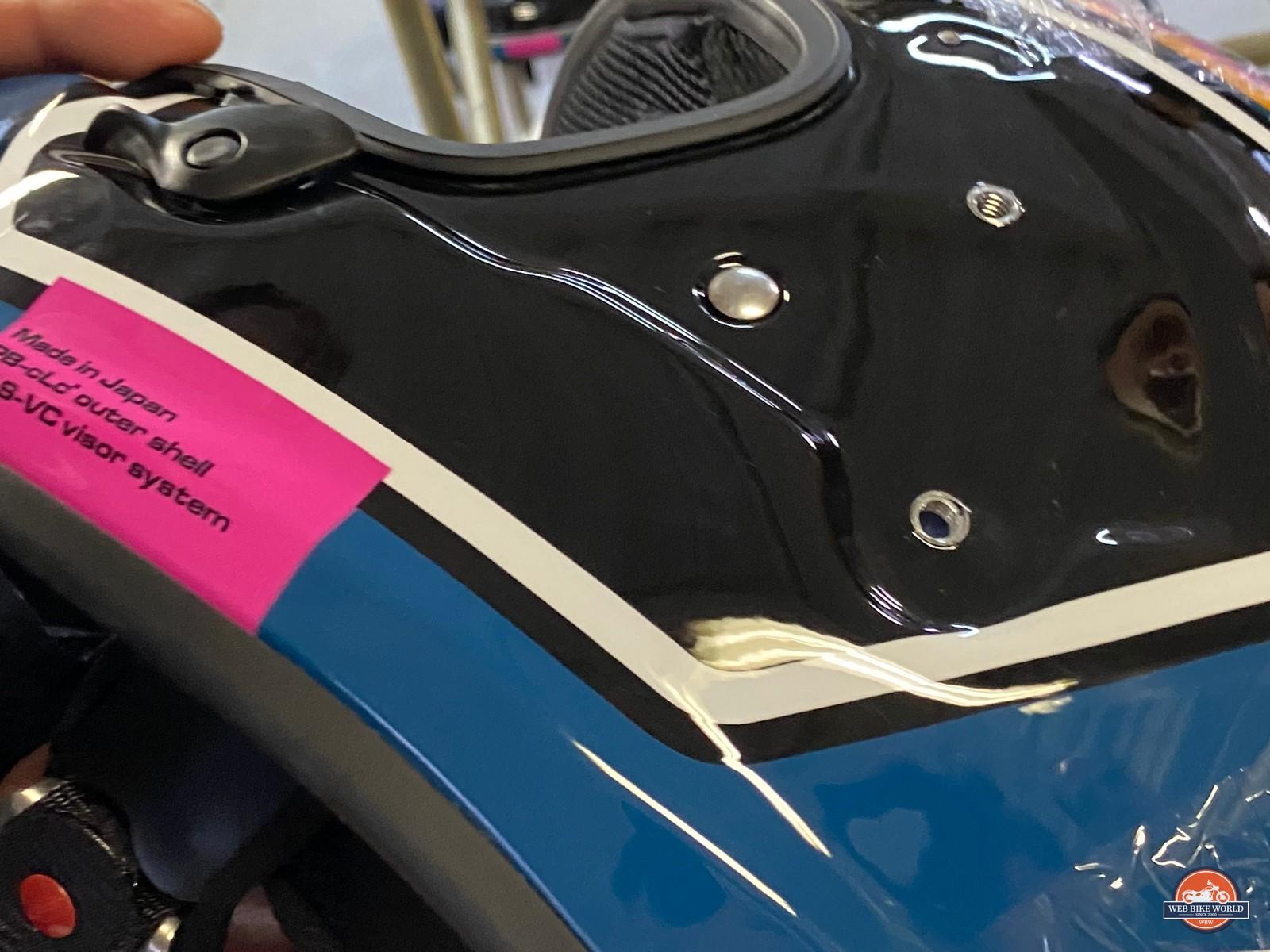 A chin strap rivet installed on an Arai helmet.