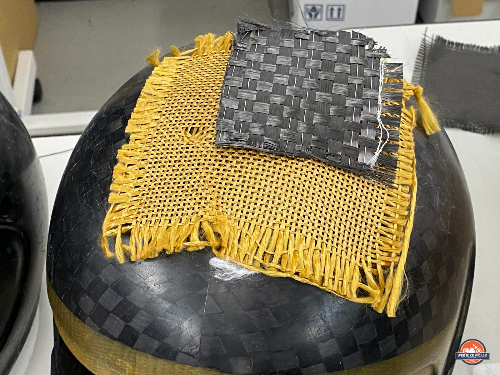 Zylon is the yellow woven material sitting on top of the carbon fiber helmet in the photo .