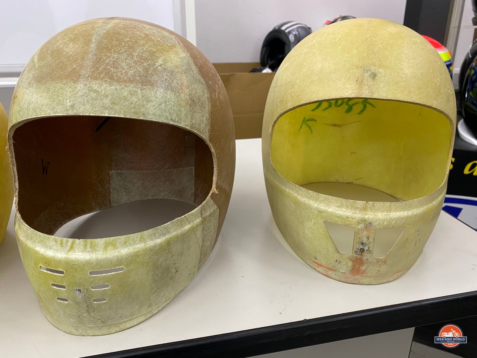 The original Arai shell is on the right and their first Kevlar shell on the left.