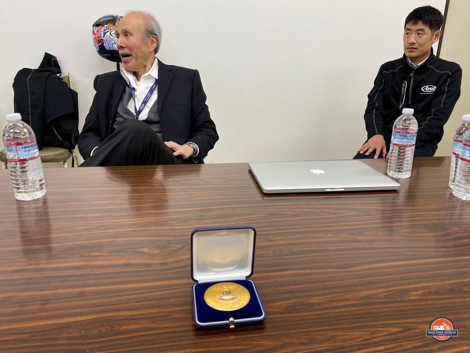 Mr. Michio Arai seated in front of the FIM Gold Medal award.
