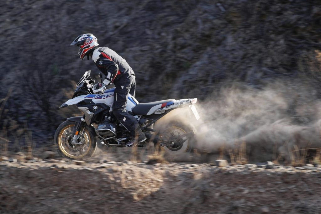 BMW adventure motorcycle riding on a dirt trail
