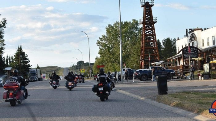 The Twin Cities Saloon in Longview, Alberta with motorcycles riding up to park in the lot.