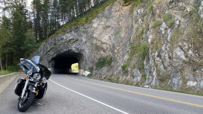 A Harley Davidson parked in front of a tunnel.