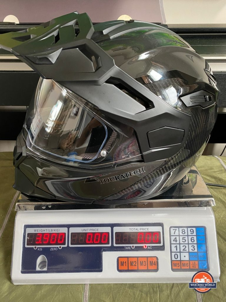 The Touratech Aventuro Traveller Carbon helmet on a scale (in pounds).