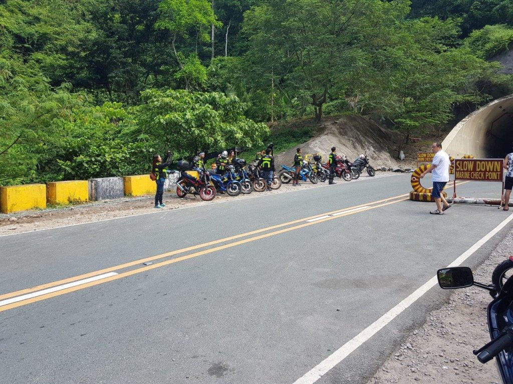 a group of bikers near a tunnel