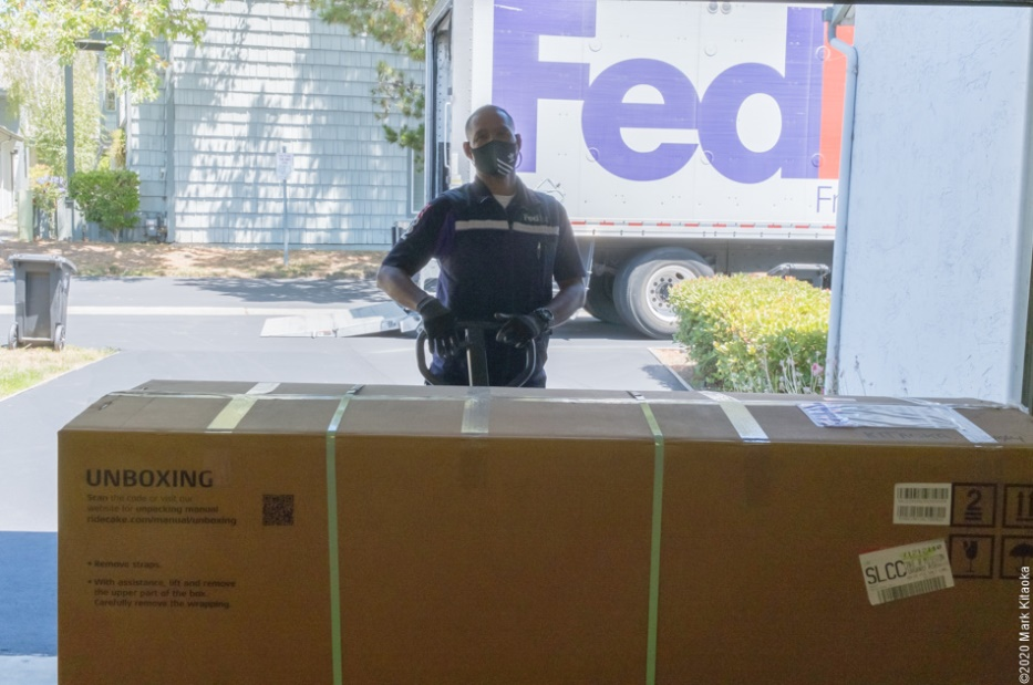 FedEx delivery man with boxed Kalk motorcycle