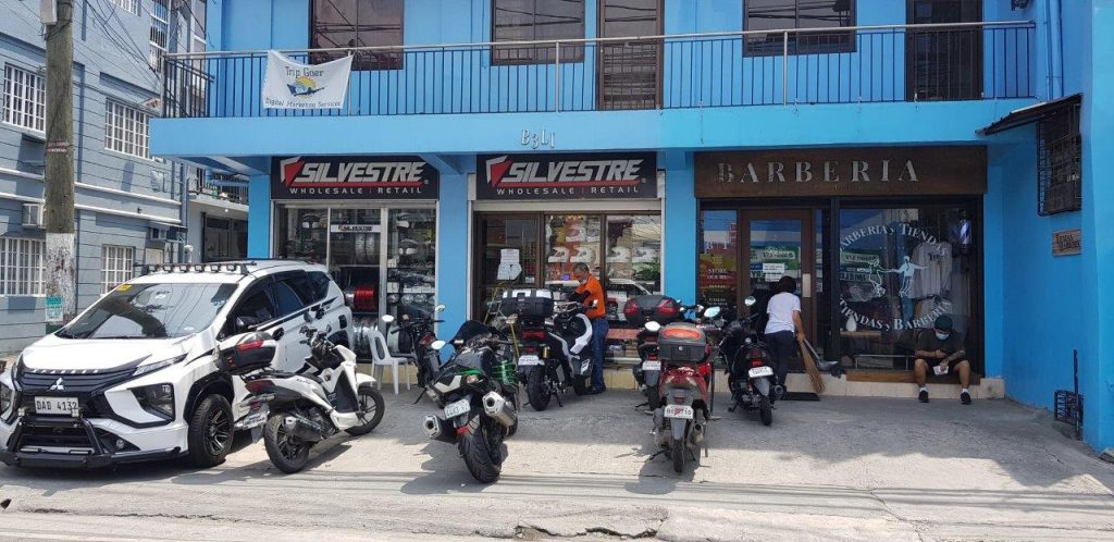 motorcycles parked outside of an auto parts shop