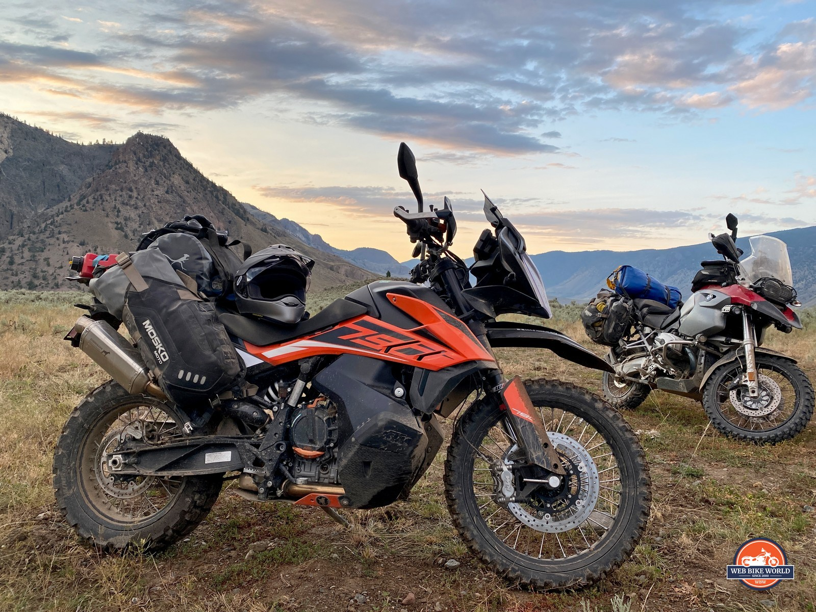 A KTM 790 Adventure and BMW R1200GS parked in front of a sunset in British Columbia, Canada.