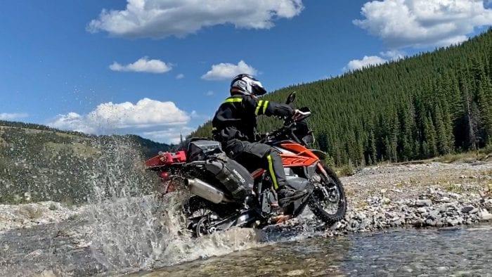 Jim Pruner riding his KTM 790 Adventure through water while wearing the Arai XD-4 helmet.