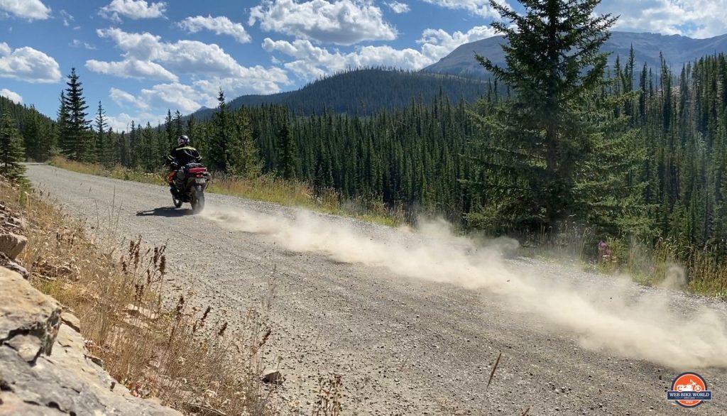 Jim Pruner riding his KTM 790 Adventure down a dusty gravel road wearing the Arai XD-4 helmet.