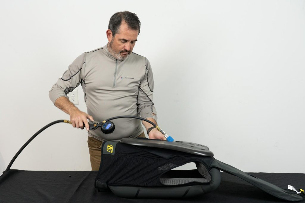 Individual inflating the Klim Ai-1 Airbag Vest with air pump.