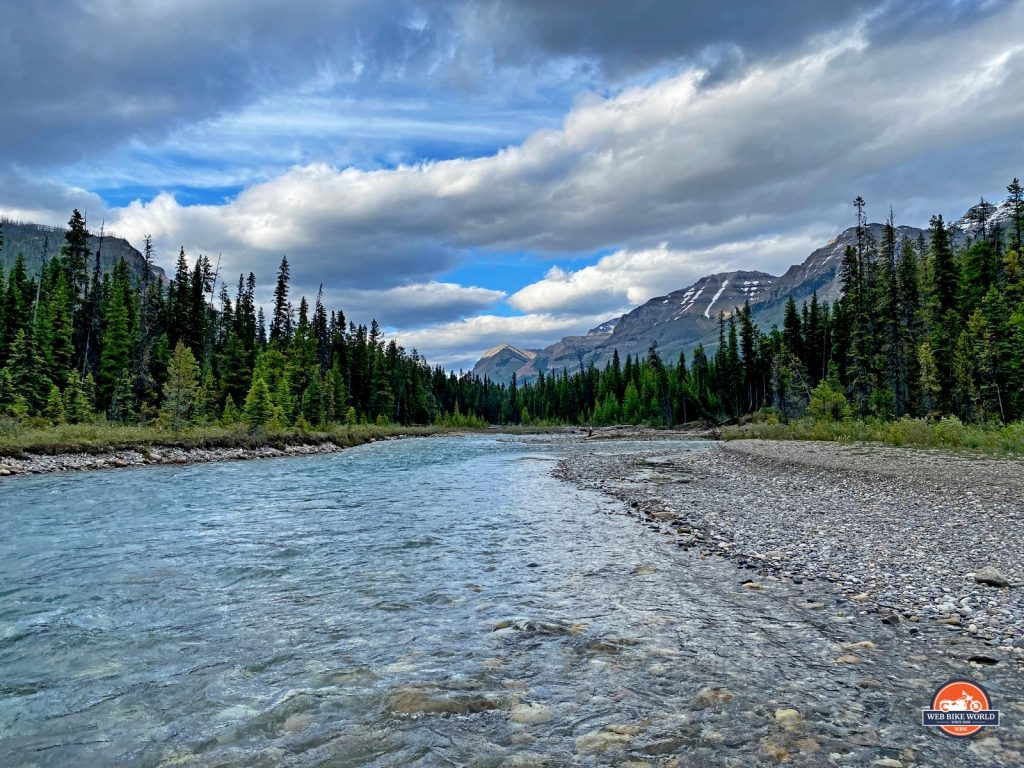 A stream running through the forests of Alberta, Canada with the Canadian Rockies in the background.