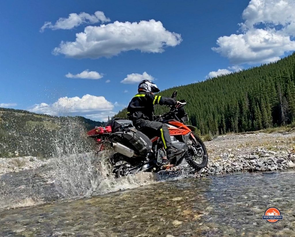 Jim Pruner riding through a stream while wearing the Joe Rocket Canada Whistler Adventure boots.
