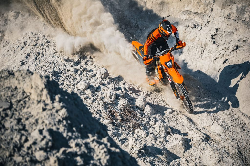 Rider climbing a soft sandy dirt hill on KTM 350 EXC-F