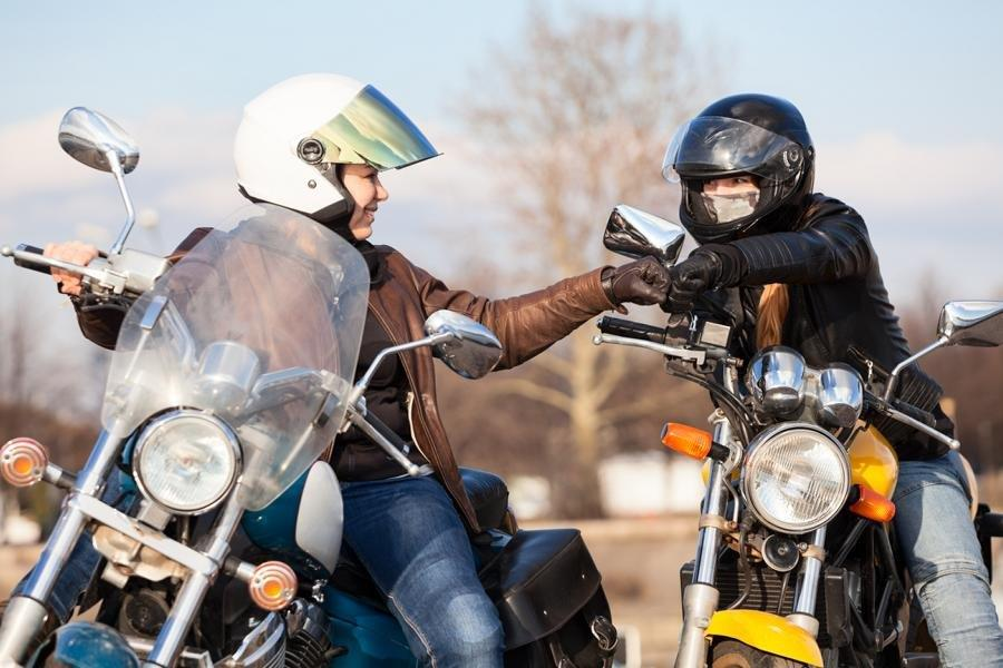 Motorcycle riders fist bumping in celebration