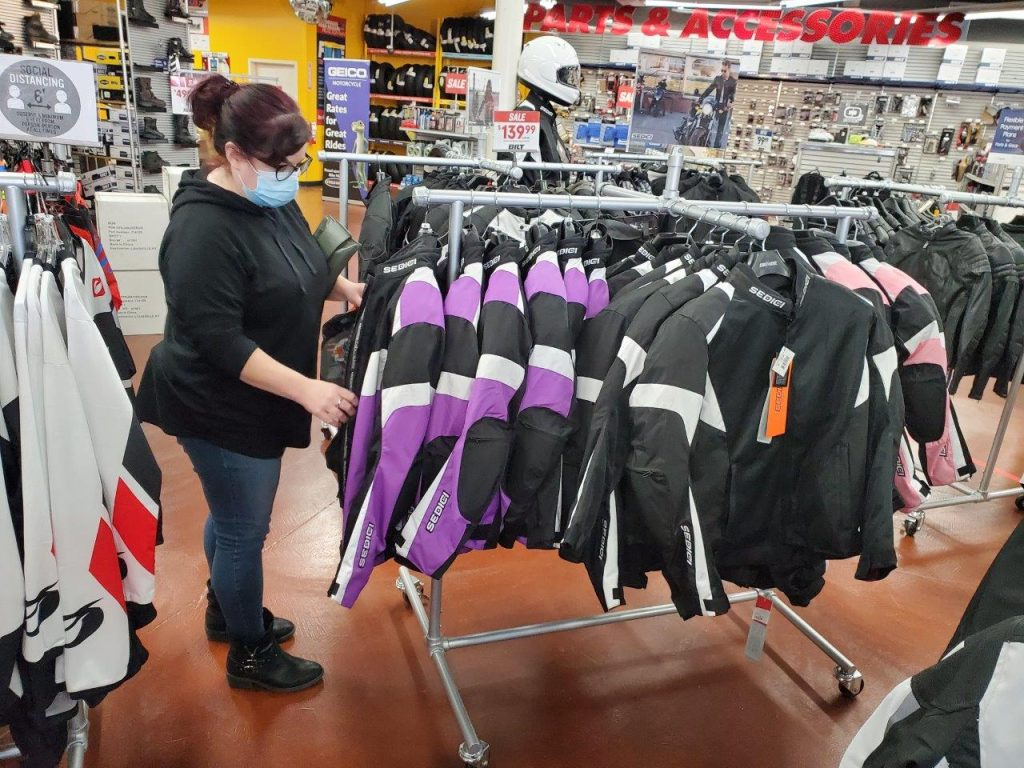 Female shopping for motorcycle jackets