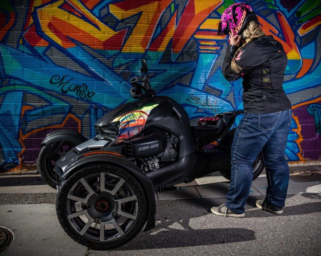 Rider Brittany Morrow putting on her motorcycle helmet