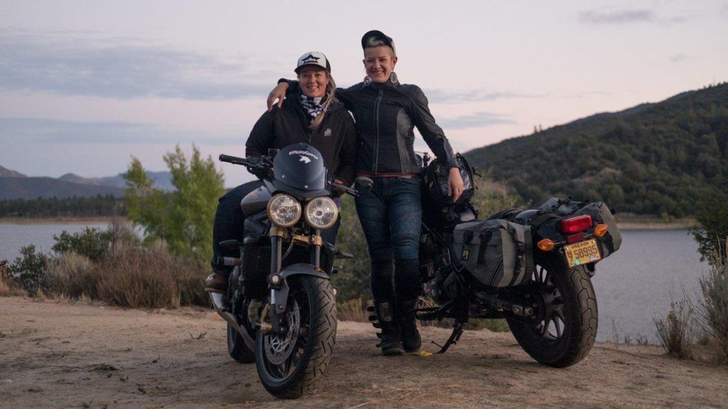 2 female motorcycle riders posing in front of lake