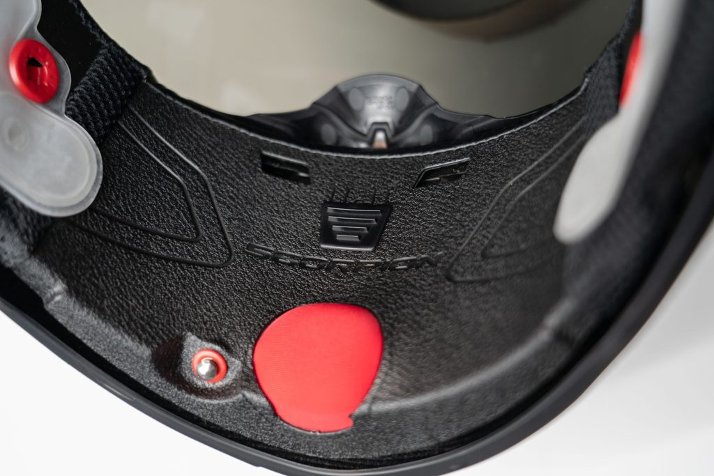Close up of helmet air release button and chin vent adjuster