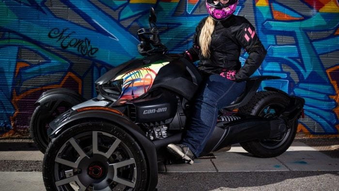 Writer Brittany Morrow on the Can-Am Ryker 900 Rally Edition in front of graffiti wall.