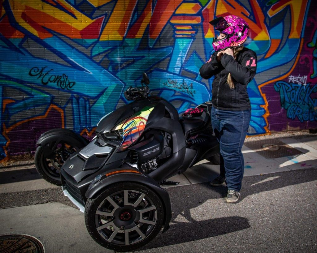 Rider adjusting her helmet next to Can-Am Ryker 900 Rally Edition