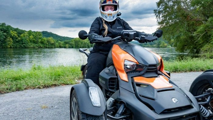 Rider on Can-Am Ryker 900 Rally Edition with lake behind her.