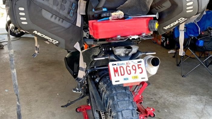 The Mosko Moto Reckless 80L V3.0 Revolver half removed from a KTM 790 adventure to access under the seat.