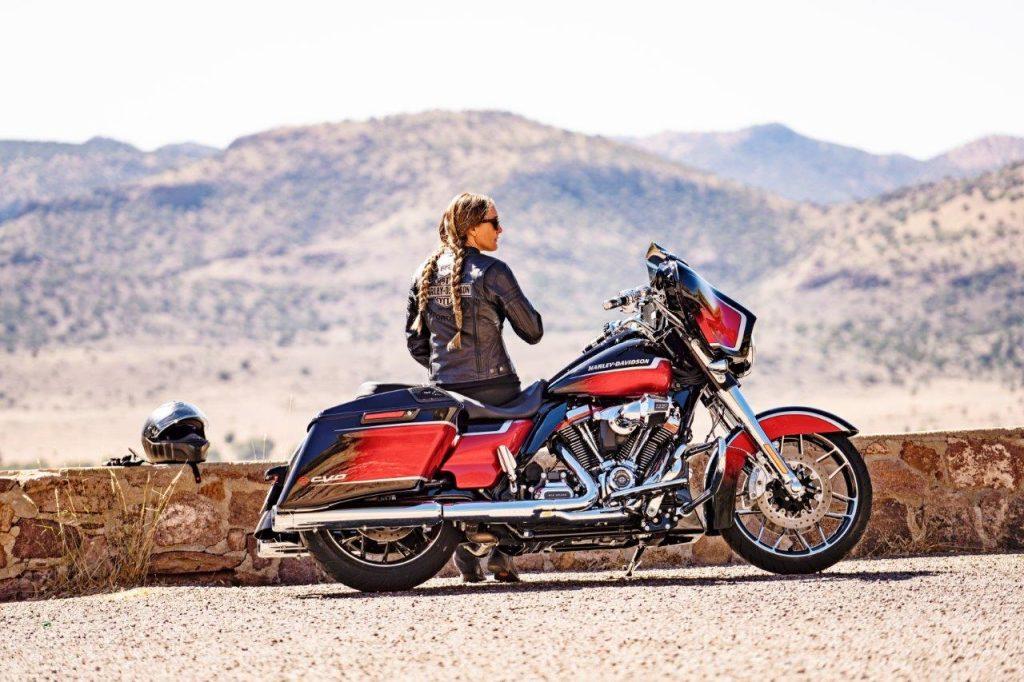 A woman rider sitting with her 2021 Harley Davidson Street Glide CVO.
