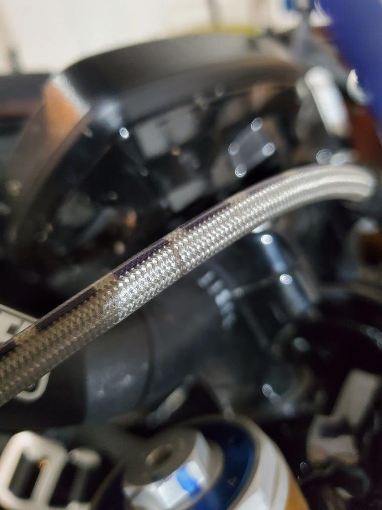 A closeup of a steel braided brake line on the Indian FTR 1200 S