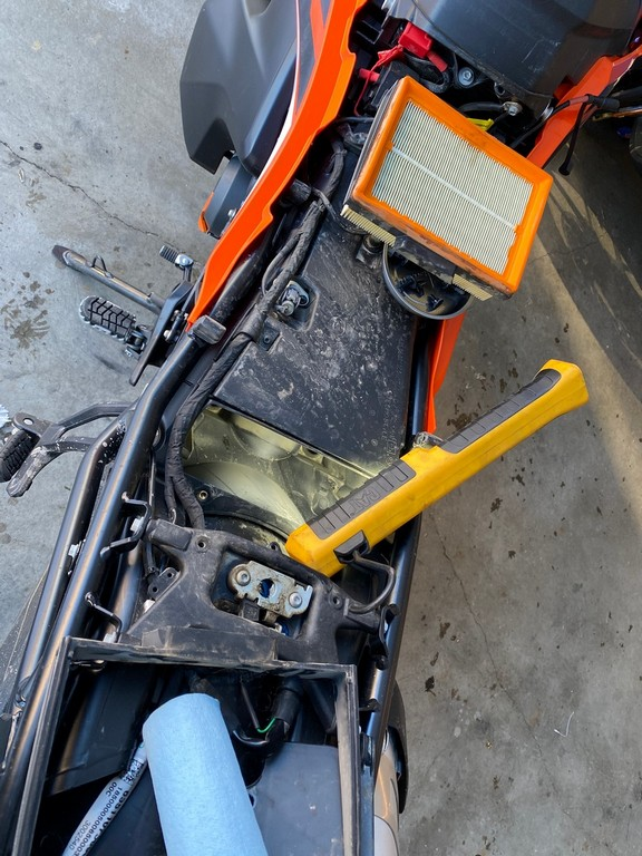 Inspecting the engine air filter on a 2019 KTM 790 Adventure.
