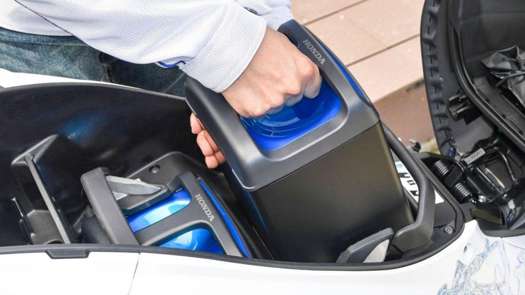 battery being placed in a vehicle likely make by Honda, Yamaha, Suzuki or Kawasaki