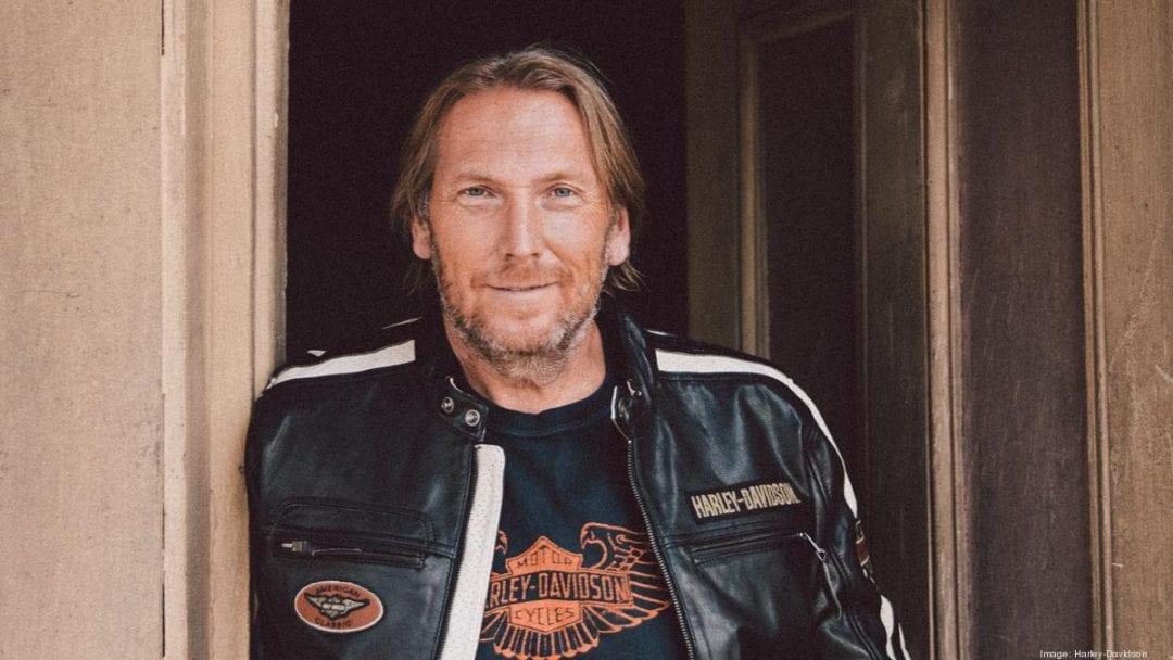 Jochen Zeitz, President of Harley Davidson, posing with a company leather jacket.