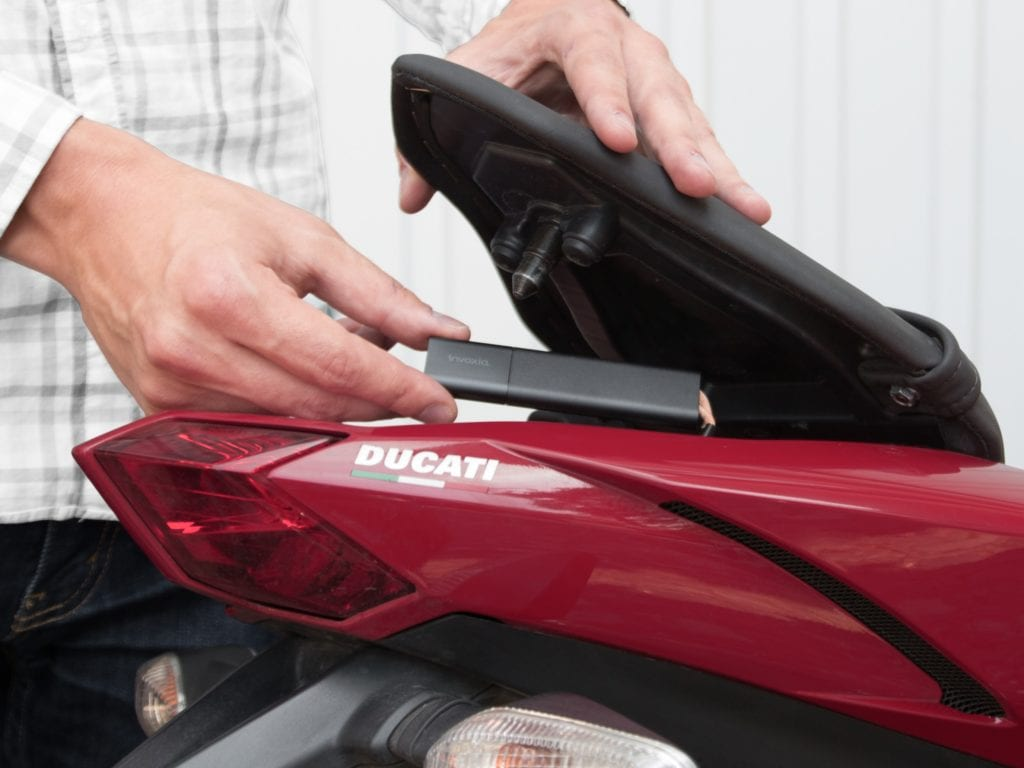 Putting the tracker in the tail storage area of Ducati/ stock photo