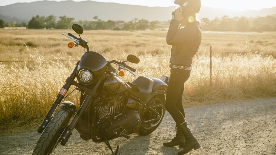 a view of a rider enjoying the tail-end of a ride, taking off her helmet in the sunset