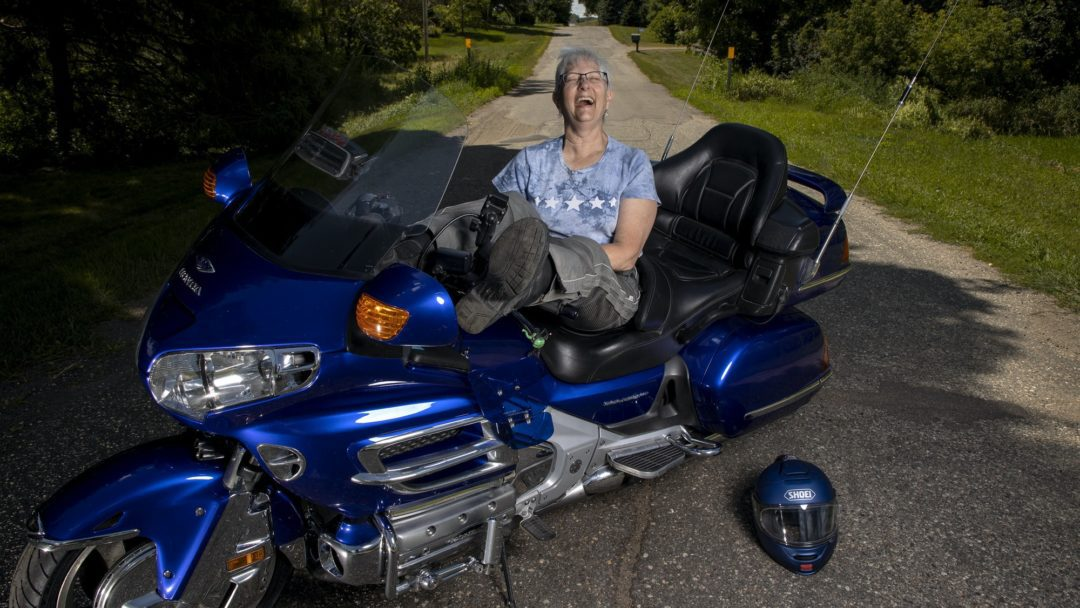 a woman leans across her motorcycle as she gets ready to ride at the three women ride for the Suffragists Centennial Motorcycle Ride