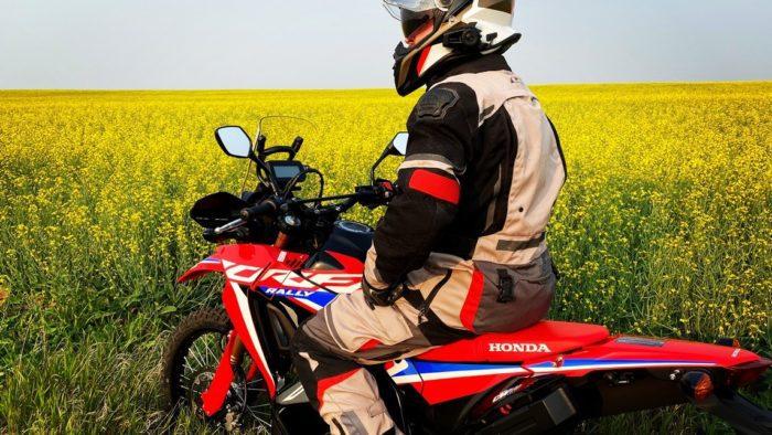 Me sitting on my 2021 Honda CRF300L Rally ABS in front of a canola field.