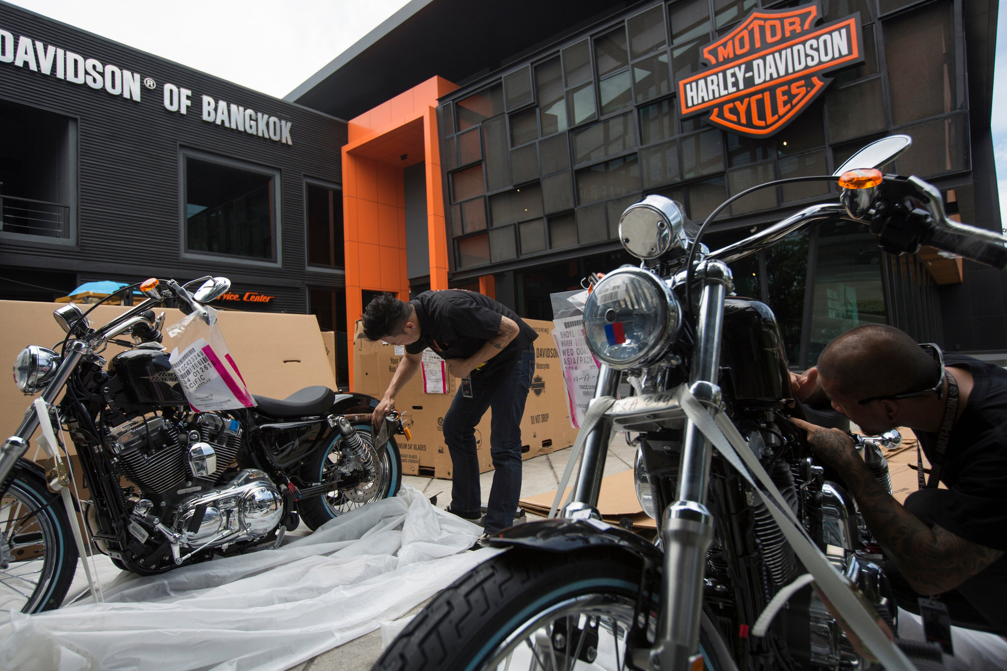 A view of H-D Dealership workers unwrapping new Harley Davidson bikes